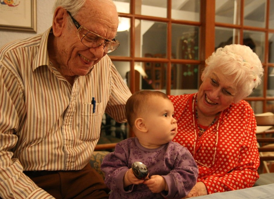 Grandparents smiling at toddler