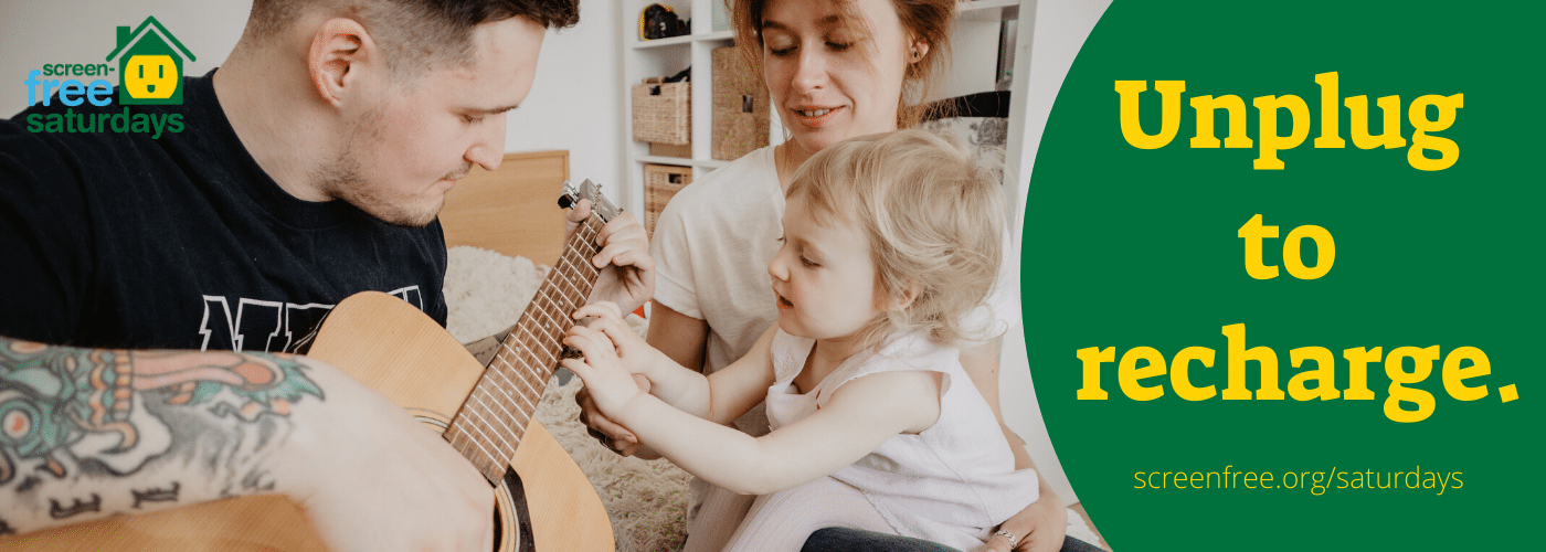 Father playing guitar with child in mother's lap