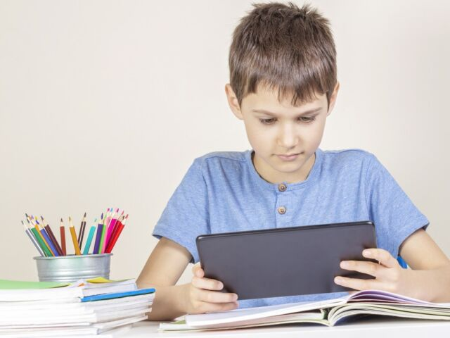 Kid with tablet computer sitting at table with books notebooks