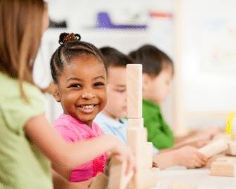 preschooler plays with wooden blocks
