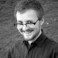 person with glasses and short hair and beard and light skin smiling, black and white photo