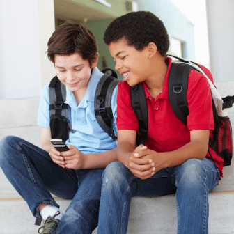 Two teens with backpacks on sit on steps, one looking at the other's phone