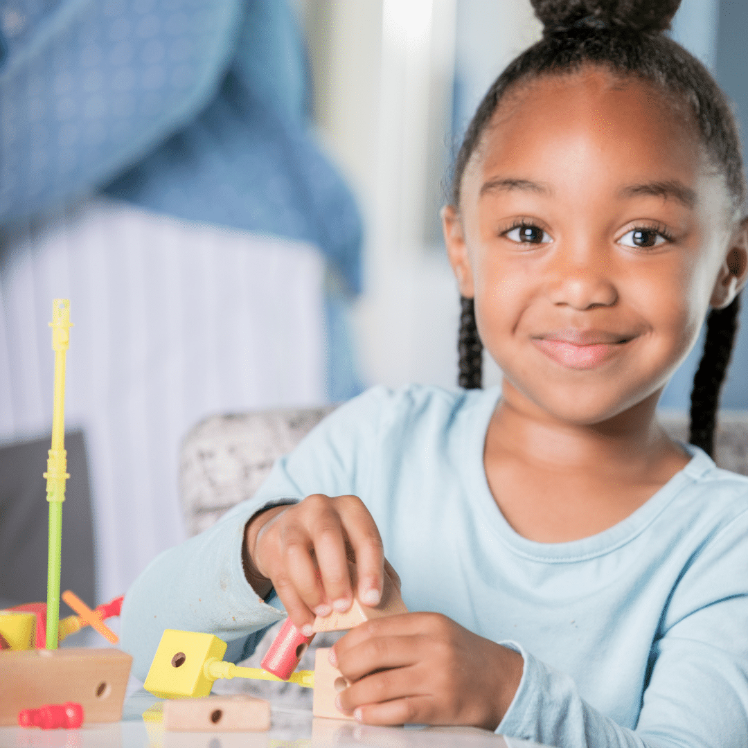 young girl smiling playing with blocks and sticks