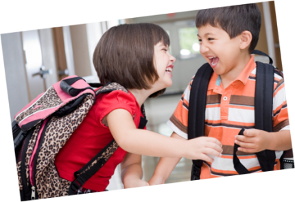 Two children at school laughing together
