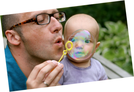 Dad blowing bubbles with baby - slider image